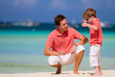 Photo for Father and son having conversation on tropical beach - Royalty Free Image