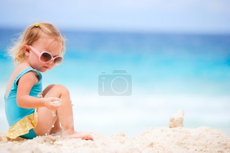 Photo for Adorable toddler girl playing on white sand beach - Royalty Free Image