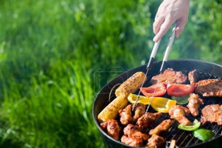 Photo for Grilling at summer weekend. Fresh meat and vegetables preparing on grill. - Royalty Free Image
