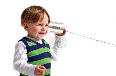Photo pour Tu m'entends ? très mignon 3-années vieux garçon décontracté habillé jouant avec le téléphone fait par soi-même. isolé sur fond blanc. - image libre de droit