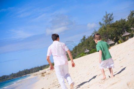 Photo pour Vacances en famille. Heureux père et fils sur la plage. Focus sur le père . - image libre de droit