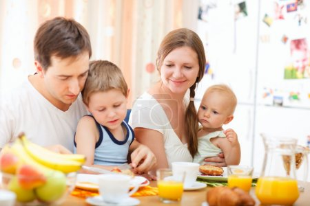 Photo for Young happy family with two kids having breakfast together - Royalty Free Image