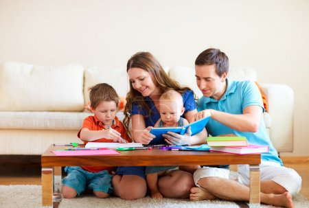 Photo for Young happy family with two kids drawing and reading together - Royalty Free Image