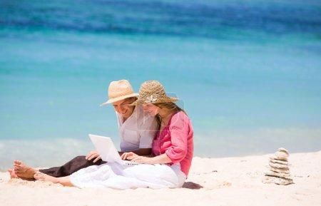 Photo pour Je cherche des vacances parfaites. Couple heureux en utilisant un ordinateur portable sur la plage . - image libre de droit