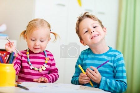 Two kids drawing with coloring pencils