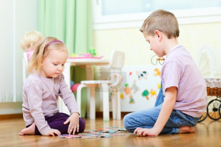 Brother and sister solving puzzle