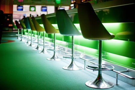 Photo for Chairs in row in bar with green lights - Royalty Free Image