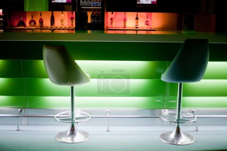 Chairs in row in bar with bottles with green lights