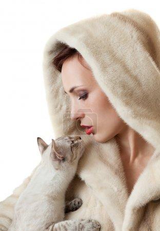 Photo pour Belle jeune fille dans un manteau de fourrure avec un chat. - image libre de droit