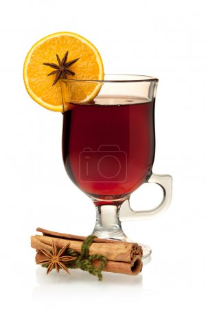 Hot mulled wine with orange slice, anise and cinnamon sticks