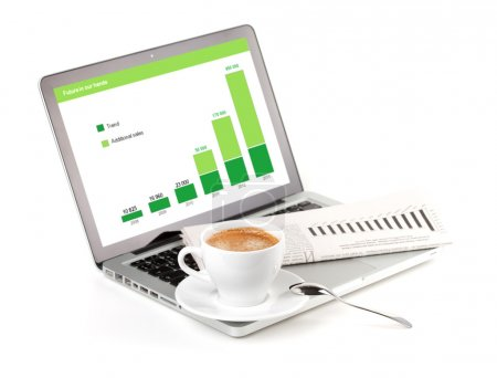 Laptop with chart, cappuchino cup and newspaper