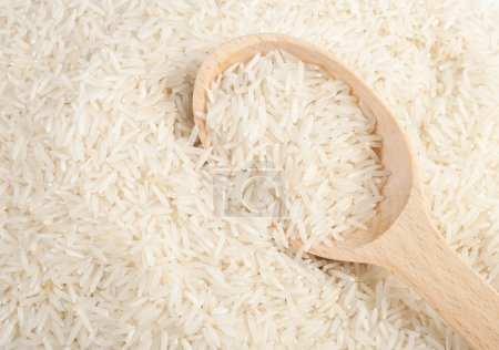 Uncooked basmati rice in a wooden spoon