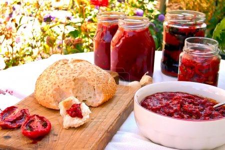Foto de Composición de tomates asados con hierbas, tarros de tomates en conserva, pimientos y pan cepillado con la mezcla de tomate-pimienta. - Imagen libre de derechos