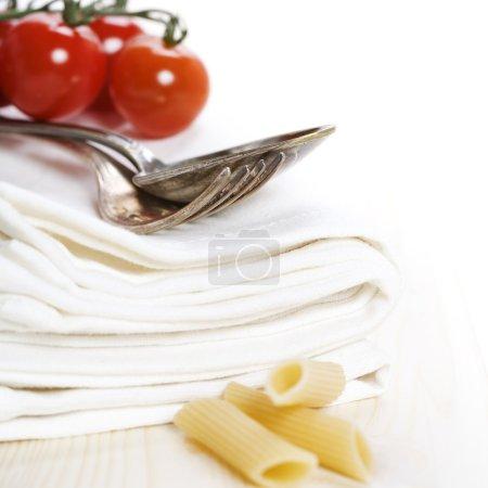 Photo pour Cuillère, fourchette, serviettes et ingrédients pour pâtes sur blanc - image libre de droit
