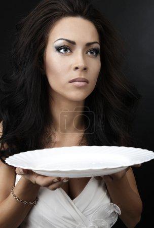 Photo pour Glamour femme avec une assiette en porcelaine blanche dans les mains - image libre de droit