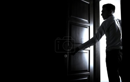 Photo for Man entering a dark room. Photo. - Royalty Free Image