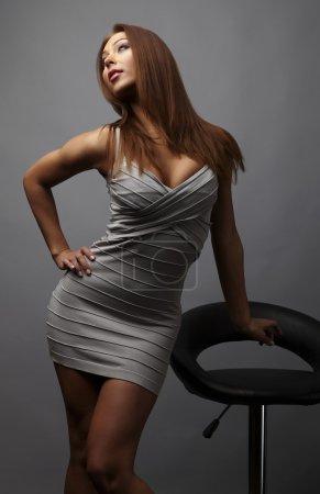 Beautiful girl pose near stylish armchair