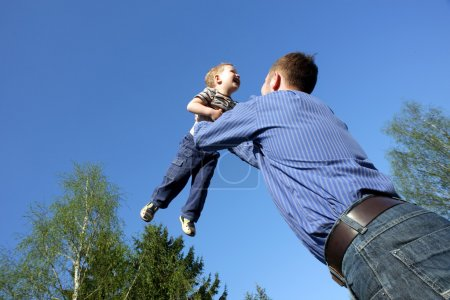Photo for Father toss up a child isolated on blue sky - Royalty Free Image