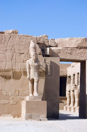 Ancient Pharaoh statue and column on backlighted sky background