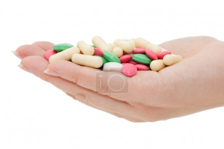 Hand with a pill on white background