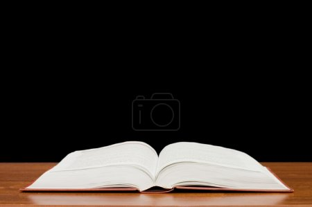 The open book on a wooden table