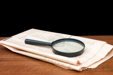 Magnify glass over a of newspaper