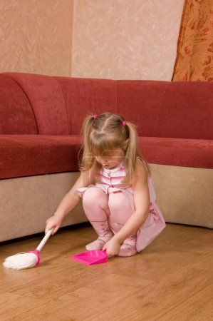 The little girl sweeps a floor