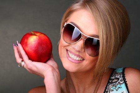 Photo pour La belle femme portant des lunettes de soleil, est titulaire d'une pomme rouge - image libre de droit