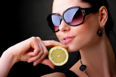 Photo pour La belle femme à lunettes de soleil avec un citron en mains. le sucre de lèvres. - image libre de droit