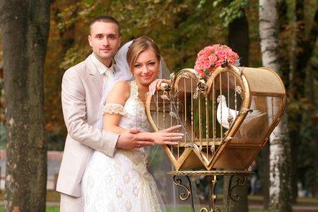 Photo pour Les coûts de couple aimant près une cage avec des pigeons blancs. - image libre de droit