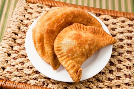 Photo for Cheese empanada, meat empanada or chicken empanada, on a white plate. Empanada (meat pie) - traditional snack originally from Spain. - Royalty Free Image