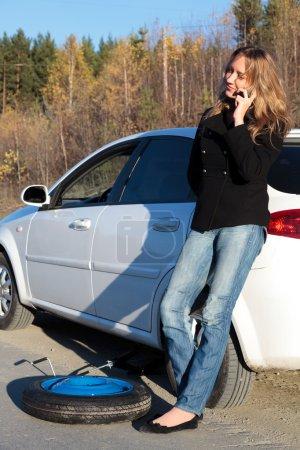 Photo pour Jeune femme debout près de sa voiture endommagée et appelant à l'aide - image libre de droit