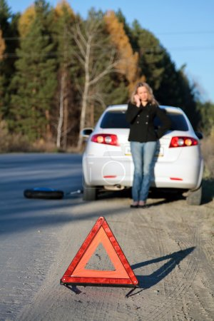 Photo for Young woman standing by her damaged car and calling for help. Focus is on the red triangle sign. Shallow depth of view. - Royalty Free Image