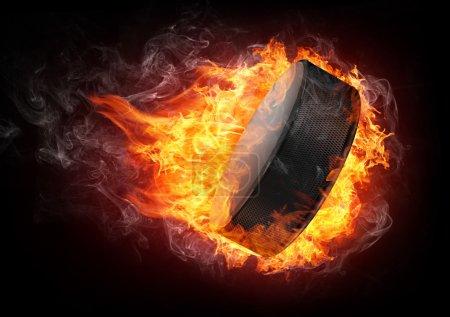 Photo pour Hockey Puck en feu isolé sur fond noir - image libre de droit