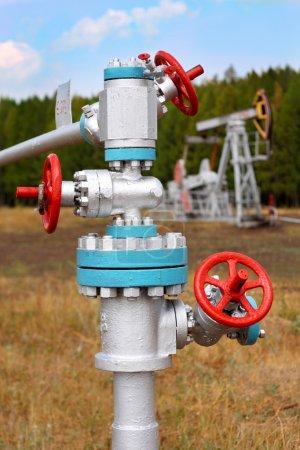 Photo pour Pipelines et vannes en acier contre ciel bleu. Le puits de pétrole rempli sur un fond . - image libre de droit
