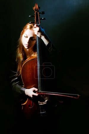 Photo for Young girl plays a violoncello against a dark blue smoke - Royalty Free Image