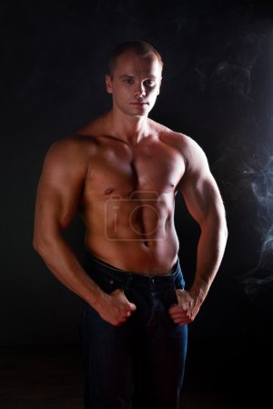 Photo for Young sporty man over Smoke. Muscles, a close up - Royalty Free Image