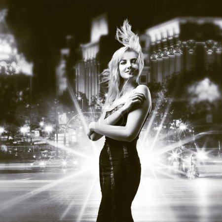 Photo pour Fille jeune beauté posant sur fond de ville de nuit - image libre de droit