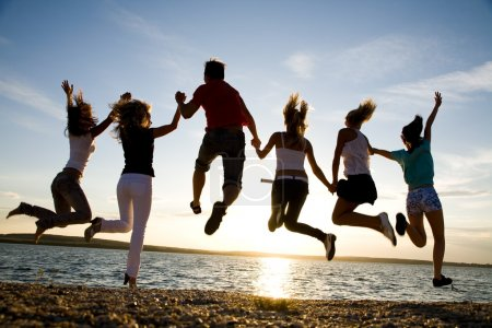 Photo for Group of happy young dancing at the beach on beautiful summer sunset - Royalty Free Image