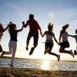 Group of happy young dancing at the beach on beaut...