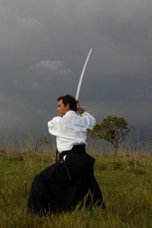 Photo pour Homme jeune aïkido avec une épée à l'extérieur - image libre de droit