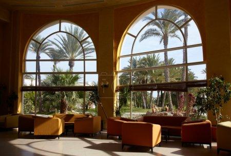 Photo pour Hall de l'hôtel avec le grand arbre de fenêtre et de palmiers à l'extérieur - image libre de droit