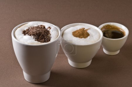 Photo for Three coffee cups with espresso, cappuccino, mochaccino over brown background - Royalty Free Image