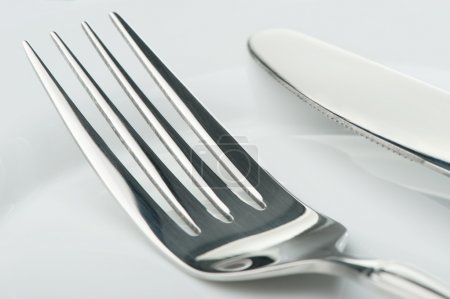 Photo for Knife and fork on a plate. Kitchen accessories close up - Royalty Free Image