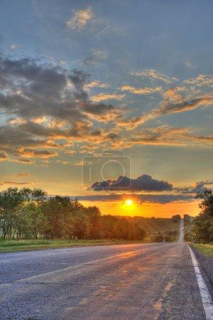 Photo pour Route et coucher de soleil. Une ligne automobile et un coucher de soleil rouge - image libre de droit