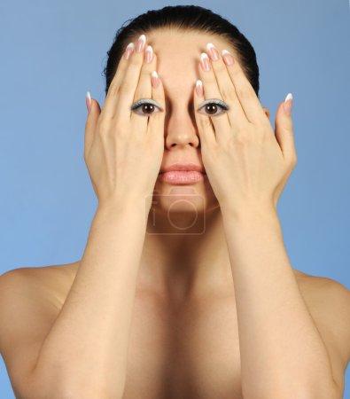 Photo pour L'image abstraite de la fille regarde à travers les doigts. Un fond bleu - image libre de droit