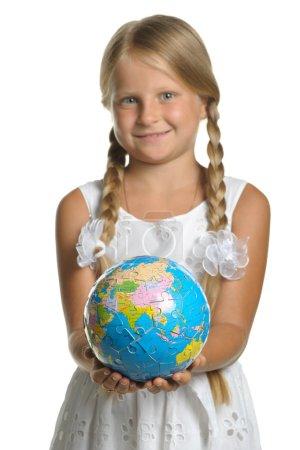 Photo pour La jeune fille détient le globe prélevé puzzle en mains. mise au point sélective. Il est isolé sur fond blanc - image libre de droit