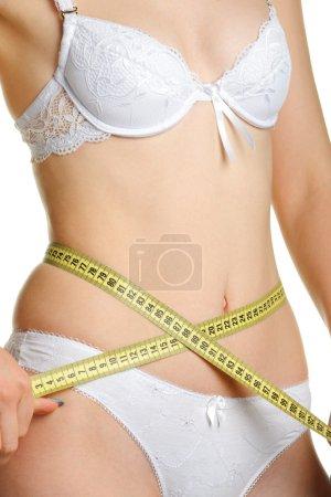 Photo pour Femme formant un corps et un ruban à mesurer. Il est isolé sur un fond blanc - image libre de droit