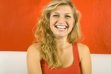 Photo for Young beautiful woman against the red wall is sitting on the sofa and laughs - Royalty Free Image