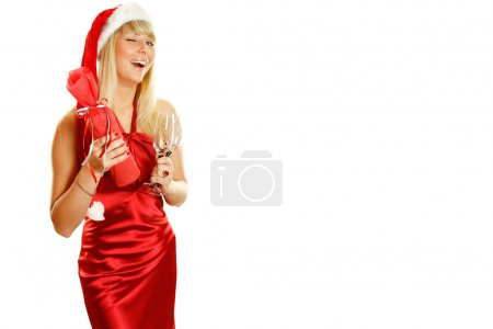 Photo for Beautiful girl in a red dress and a Christmas hat in his hands and two glasses of boxed wine/ champagne bottle. Winks. Isolated on a white background - Royalty Free Image
